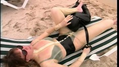 Tied fetish slave cleans her mistress with her tongue on the beach