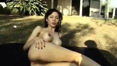 Big breasted Oriental milf Maya Chung poses nude for the camera outside