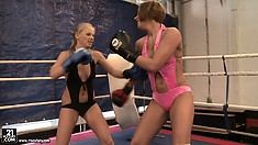 Two bitches in skimpy bathing suits face each other in the ring